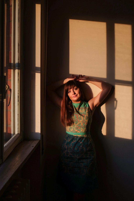 portret kobiety przez okno zlota godzina