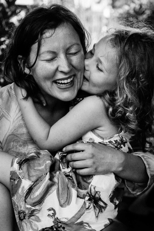 czarno-białe zdjęcie przedstawiające roześmiane mamę i córkę