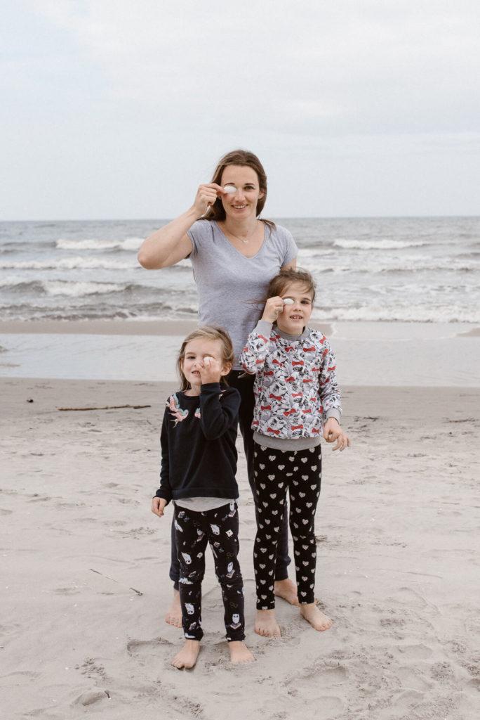Mama i dwie córki na plaży nad morzem trzymają muszelki