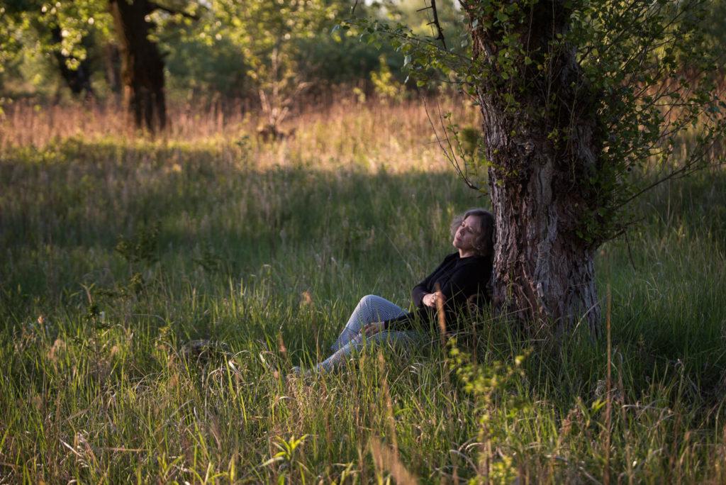 Sesja wizerunkowa o świcie, kobieta siedzi pod drzewem