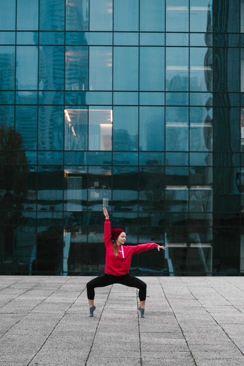 kobieta w czerwonej bluzie tańczy w mieście