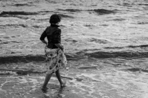 kobieta w sukience i czarnej kurtce wchodzi do morza
