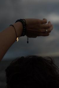 ręka z bransoletką ze złotą błyskawicą