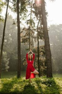 kobieta w czerwonej sukience w pozycji drzewa